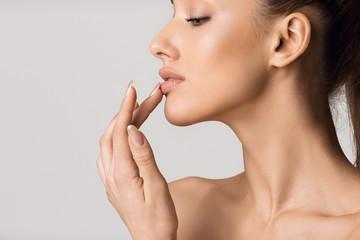 Lip augmentation. Beautiful girl touching her lips