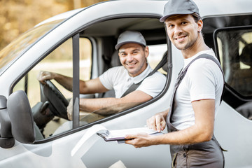 Portrait of a cherfull delivery company employees in uniform delivering goods by cargo van vehicle, mover with a car driver checking delivery list