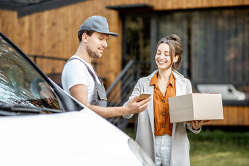 Delivery company employees in uniform delivering goods to a client by car, woman signing on a...