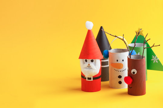 Merry christmas toy collection santa claus, snowman, tree, reindeer on yellow for Winter holiday concept background. Paper crafts, DIY. creative idea from toilet roll
