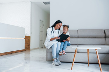 Female doctor with notepad sits in the clinic with little girl