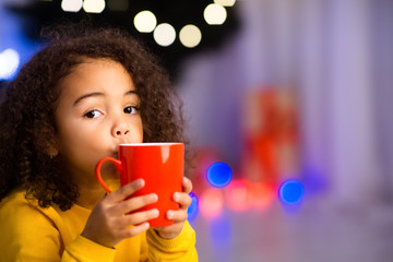 Funny african girl with cup of warm winter cocoa