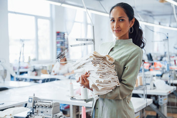 Woman dressmaker stands in the factory with cloth in hands