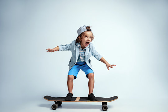 Pretty young boy on skateboard in casual clothes on white studio background. Riding and looks happy. Caucasian male preschooler with bright facial emotions. Childhood, expression, having fun.