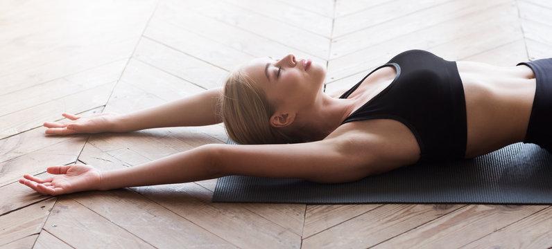 Relaxed girl laying on yoga mat, morning exercising