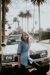 Young woman posing in Beverly Hills in front of car