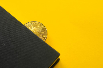 gold coin bitcoin in a notebook on a yellow background. space for text