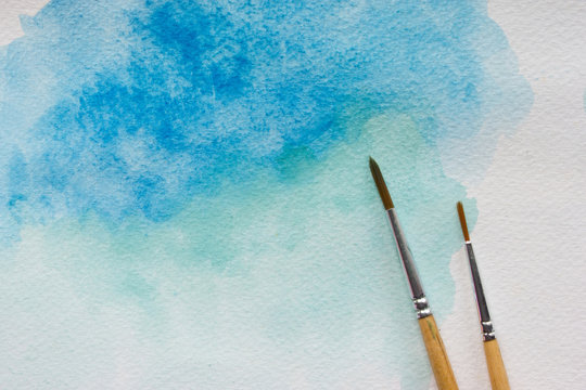 Paintbrushes on isolated watercolor painted background.