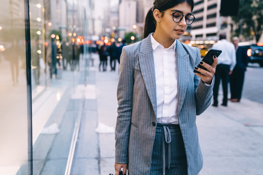 Female expert in formal wear standing at city urban area for writing feedback to client using modern mobile phone with applications, Spanish business woman in optical eyewear reading email
