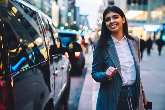 Businesswoman smiling while looking at camera near black SUV at night