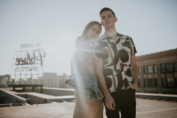 Young urban couple posing on sunny rooftop