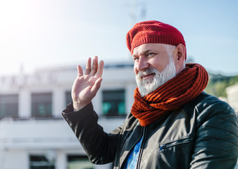 Aged  cheerful sailor dressed in red hat and scarf. Good-natured Senior waving hand