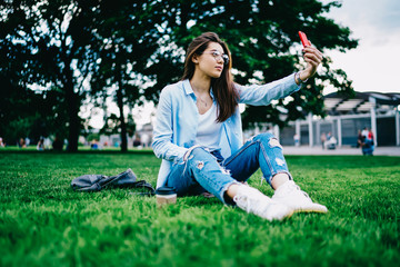 Young woman in spectacles posing for selfie on smartphone camera sitting in park during free time,hipster girl taking photo on mobile phone for blogging recreating on free time in college campus