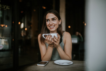 young woman smiling with coffee in cafe
