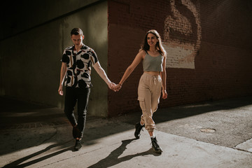 Young urban couple holding hands on a sunny afternoon walk