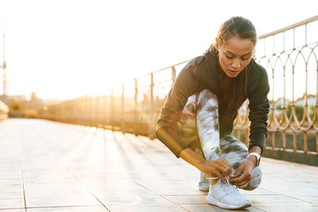 Image of young athletic woman tying shoelaces while working out