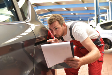 Car mechanic examines accident vehicle in a workshop after painting