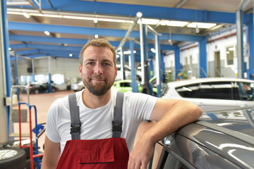 Portrait of a smiling car mechanic in a professional workshop - closeup photo