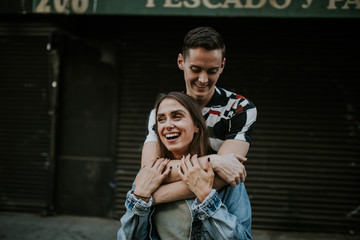 Young laughing couple embracing in urban area