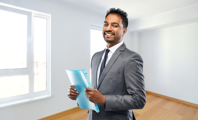 real estate business and people concept - indian man realtor with folder over empty new apartment...