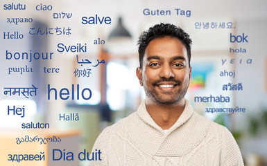 communivation, translation and international concept - smiling indian man in knitted woolen sweater...