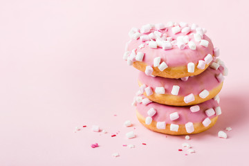 Fototapete - Tower of pink glazed donuts with marshmallows on pink background