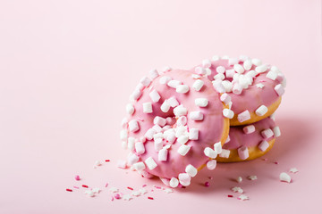 Wall Mural - Pink glazed donuts with marshmallows on pink background