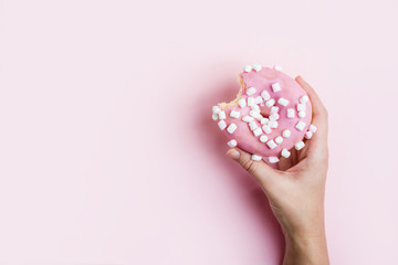 Wall Mural - Female hand holding pink bitten donut over pink background. Delicious dessert or diet stall concept