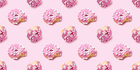 Wall Mural - Seamless texture with Bitten icing donut on pink background, isometric view