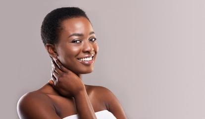 Fototapete - Smiling beautiful black girl touching her soft skin on neck