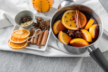 christmas and seasonal drinks concept - pot with hot mulled wine, orange slices, aromatic spices...