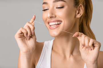 Dental care. Young woman using dental floss