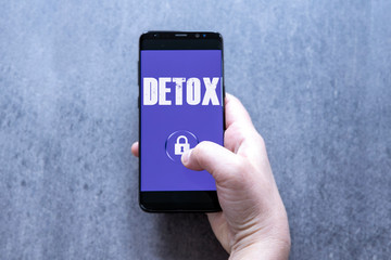 Digital detox concept female hand holding smartphone with text detox and lock symbol on the button.