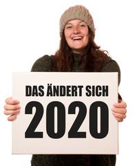 Junge fröhliche Frau hält Schild: Das ändert sich 2020