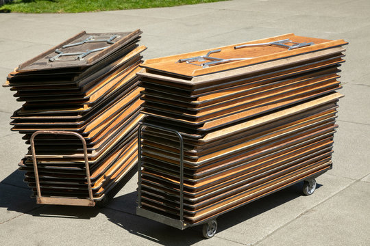 Stack of folding banquet tables on a push cart