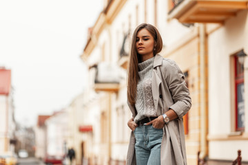 Stylish urban young woman in a fashionable knitted sweater in a elegance trench coat in a blue jeans posing in the street. European modern cute model girl enjoys a walk in the city. Spring fashion.