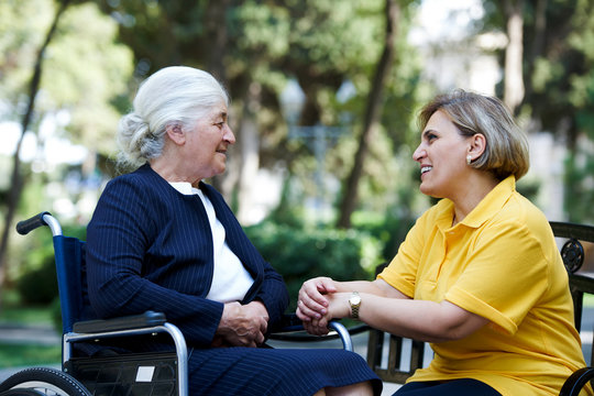 Professional helpful caregiver and handicapped senior woman.