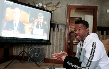 Voter Quincy Murphy watches the public hearing held by the House Permanent Select Committee on Intelligence as part of the impeachment inquiry into U.S. President Donald Trump, in his home in Flint