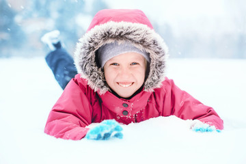 Portrait of cute Caucasian smiling excited girl child in pink jacket playing with snow lying on ground during cold winter snowy day at snowfall. Kids outdoor seasonal activity. Funny face.