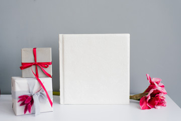 Classic photo album in a leather white cover surrounded by gift boxes and a pink flower on a gray background