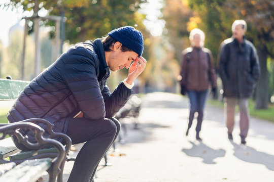 Worried young man on a bench during autumn day