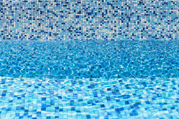 Empty pool, blue water and mosaic tiling pattern