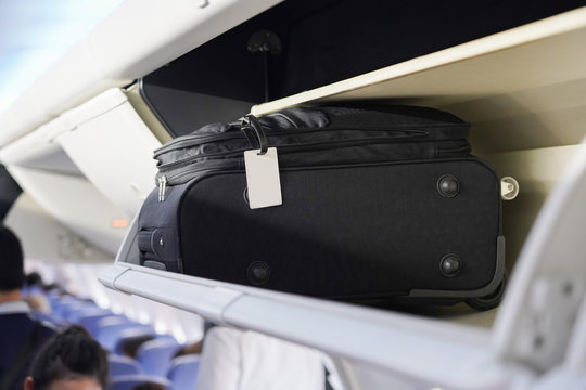 view of carry on luggage on overhead shelf in the airplane cabin