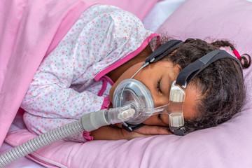 Child suffering from Sleep Apnea, wearing a respiratory mask.