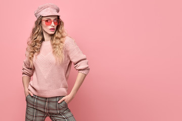 Wall Mural - Fashionable woman in Trendy pink outfit, stylish hairstyle, makeup. Young blonde in jumper, cap. Sensual beautiful model girl in stylish sunglasses, pastel fashion beauty concept on pink