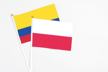 Poland and Colombia stick flags on white background. High quality fabric, miniature national flag. Peaceful global concept.White floor for copy space.