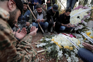 People read the Quran during the funeral of Muath al-Ajouri, son of Islamic jihad official, at Yarmouk Palestinian camp in Damascus