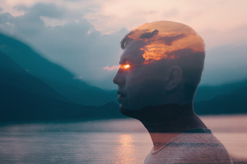 Young man profile portrait on the background of sunset mountains and sea lake. Fire and ray from the eyes. Multiple exposure image.