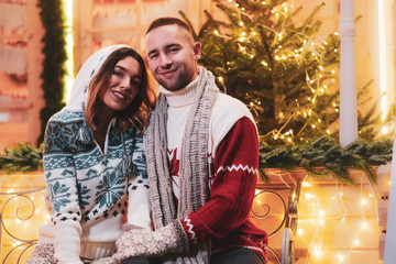 Young attractive couple spending time together on Christmas day near christmas tree.