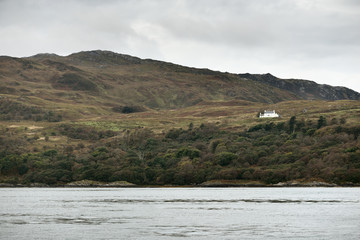 Panoramic view of the cliffs, mountains and valleys of the islands of Inner Hebrides on a cloudy day. Scotland, UK. Lonely house close-up